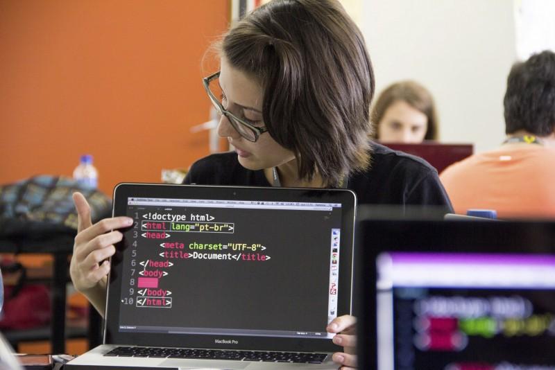 Mulher mostra códigos durante programação com software livre