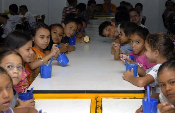 Crianças na mesa comem merenda