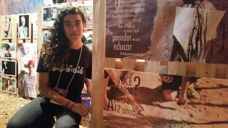 Autora de uma das fotos, Leydiane Tiano, de 20 anos, ao lado da exposição Multiverso Expressivo