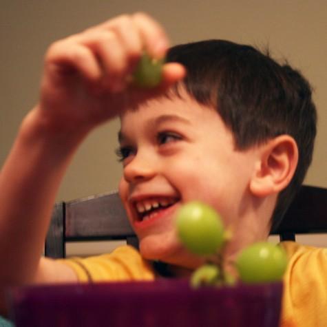 Menino comendo uvas