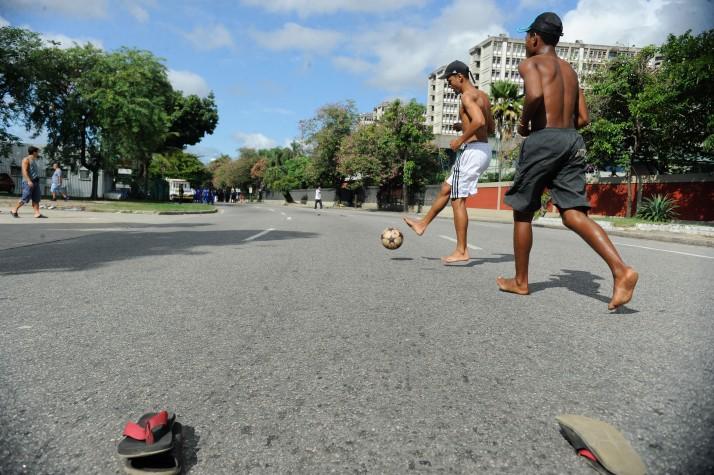 Meninos jogam futebol de rua e interagem com turistas