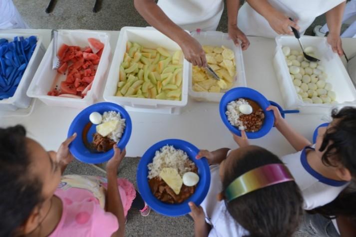 crianças comendo comida na escola