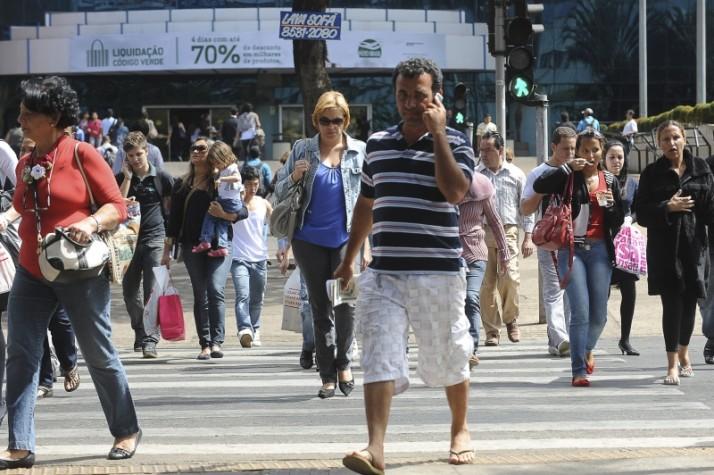 Homem fala ao celular em meio à multidão atravesando a rua