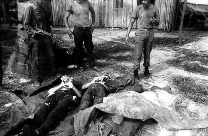 Homens armados olham para corpos que estão no chão, cobertos com um lençol branco