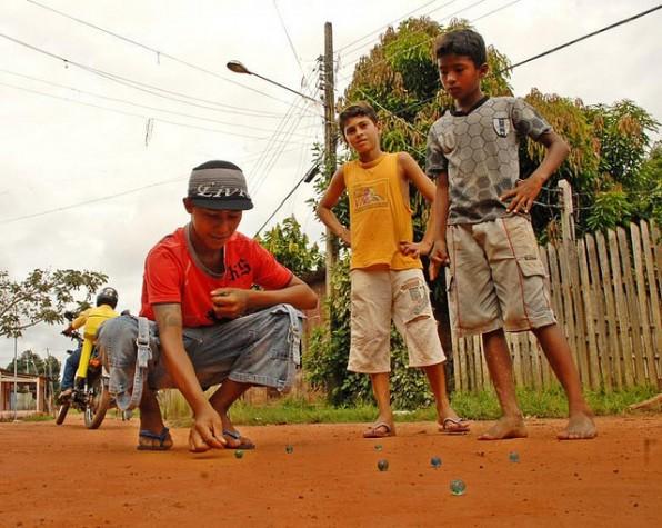 Crianças brincam com bolinha de gude