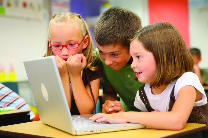 Crianças usando computador em sala de aula