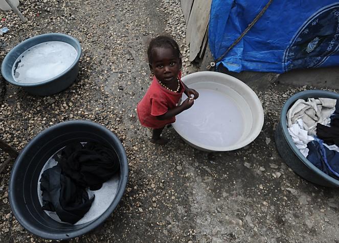 Bebê negro, vestindo uma camisa vermelha, olha para o fotógrafo, que o clicou de cima. Ela está no meio de três bacias com água.