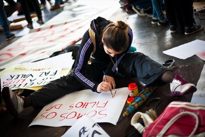 Estudante faz cartaz para manifestação